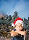 Jongen die in Santa Claus-hoed op pijnboombos glimlachen Royalty-vrije Stock Foto