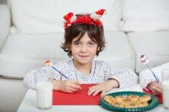 Jongen die Santa Headband Writing Letter At-Huis dragen stock fotografie