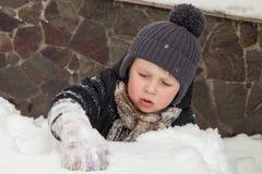 Jongen die in sneeuw wordt geplakt Stock Afbeeldingen