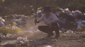 Jongen die in stortplaats buigen stock footage