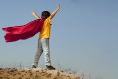 Jongen die superheroes op de hemelachtergrond spelen, tienersuperhero stock foto