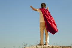 Jongen die superheroes op de hemelachtergrond spelen, tienersuperhero Stock Afbeeldingen
