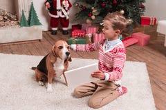 Jongen die tablet tonen aan hond op Kerstmis royalty-vrije stock fotografie
