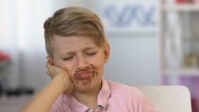 Jongen die tandpijn aan vuil gezicht lijden dat in chocolade, kind het te veel eten snoepjes wordt behandeld stock footage