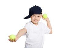 Jongen die tennisballen werpt Stock Foto