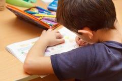 Jongen die thuiswerk met kleurenpotlood doet Royalty-vrije Stock Afbeeldingen