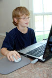Jongen die thuiswerk op computer doet stock fotografie