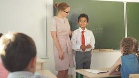 Jongen die toevoeging en aftrekking aan boord oplossen schooljongen het schrijven oplossing van wiskundige verrichting stock footage