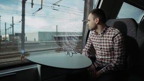 Jongen die uit buiten treinvenster, in de avond, reis kijken 4K Verduisterende jongen in venster Stadsmeningen stock footage