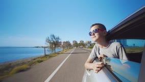 Jongen die uit het autoraam kijken De zomerreis met familie stock footage