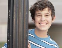 Jongen die van achter een pool glimlacht stock fotografie
