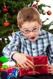Jongen die van de inhoud van zijn Kerstmisgift wordt verbaasd Royalty-vrije Stock Afbeeldingen