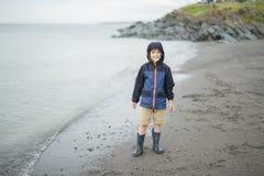 Jongen die van de regen genieten en pret buiten op het strand hebben grijze regenachtig Royalty-vrije Stock Fotografie