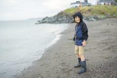 Jongen die van de regen genieten en pret buiten op het strand hebben grijze regenachtig Royalty-vrije Stock Foto's