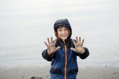 Jongen die van de regen genieten en pret buiten op het strand hebben grijze regenachtig Royalty-vrije Stock Afbeeldingen
