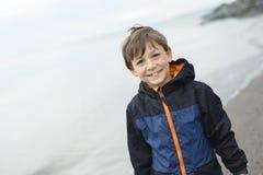 Jongen die van de regen genieten en pret buiten op het strand hebben grijze regenachtig Stock Foto's