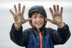 Jongen die van de regen genieten en pret buiten op het strand hebben grijze regenachtig Stock Fotografie