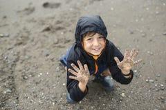 Jongen die van de regen genieten en pret buiten op het strand hebben grijze regenachtig Stock Afbeelding