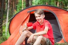 Jongen die van de zomer in het kamperen genieten stock foto's