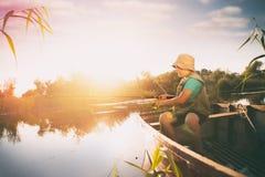 Jongen die van houten boot vissen en hengel houden stock afbeelding