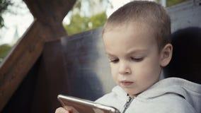 Jongen die van twee jaar op een bank in de park en het letten op beeldverhalen op een smartphone zitten stock footage