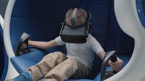 Jongen die van virtuele werkelijkheidsaantrekkelijkheid genieten die VR-hoofdtelefoon als bewegende interactieve voorzitter met b stock footage