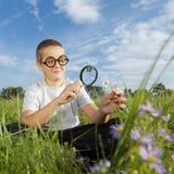 Jongen die Vergrootglas met behulp van royalty-vrije stock foto