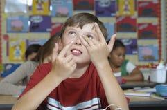 Jongen die Vingers in Klaslokaal gebruiken Te tellen royalty-vrije stock afbeeldingen