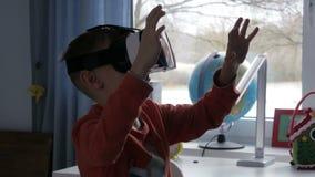 Jongen die in virtuele werkelijkheidsglazen 360 graad op video letten - 4k stock video