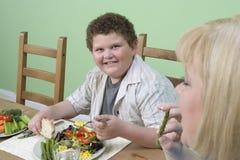 Jongen die Voedsel met Moeder hebben thuis Stock Foto