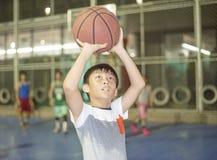 Jongen die voor basketbal voorbereidingen treffen die bij sportterrein schieten Royalty-vrije Stock Foto