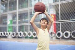 Jongen die voor het schieten bij basketbalhof voorbereidingen treffen stock afbeeldingen