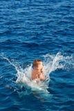 Jongen die in Water springen stock afbeelding