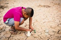 Jongen die weinig groene boom op barst droge grond planten royalty-vrije stock afbeeldingen
