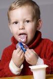 Jongen die yoghurt eet royalty-vrije stock afbeelding