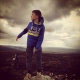Jongen die zich bovenop een rots bevinden Stock Afbeelding