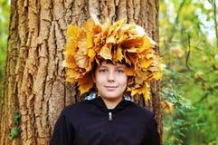 Jongen die zich in de herfstpark bevinden op een achtergrond van bomen Bij het hoofd van geweven kroon van de herfstbladeren royalty-vrije stock foto