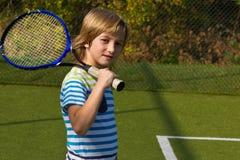 Jongen die zich met tennisracket en bal bevinden op het hof Stock Afbeeldingen