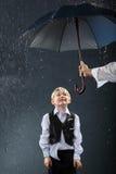 Jongen die zich onder paraplu in regen bevindt Royalty-vrije Stock Foto's