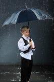 Jongen die zich onder paraplu in regen bevindt Stock Foto