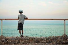 Jongen die zich op kade in de schemer bevindt die op zee kijkt Stock Foto's