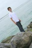 Jongen die zich op rotsen bij het strand bevindt stock afbeeldingen