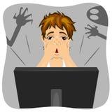 Jongen die zijn gezicht behandelen terwijl het letten van verschrikkings op film op Internet De schaduw van spook is op muur Royalty-vrije Stock Afbeeldingen