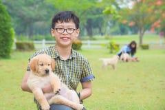 Jongen die zijn hond en glimlachen in park houdt stock afbeeldingen