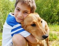 Jongen die zijn hond koestert Stock Fotografie