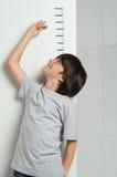 Jongen die zijn hoogte meten stock afbeeldingen