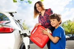 Jongen die zijn moeder helpen om brandstof in autotank te gieten stock foto