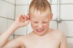Jongen die zijn oor in de douche schoonmaken Stock Foto's