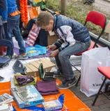 Jongen die zijn verdiend geld op queensday markt tellen royalty-vrije stock foto