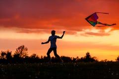 Jongen die zijn vlieger vliegen tegen een spectaculaire zonsondergang Royalty-vrije Stock Foto's